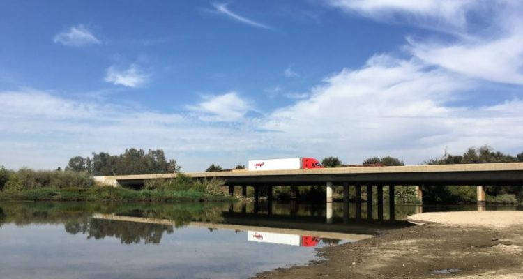 Photo of a big rig crossing a bridge on Highway 99 over the Kings River