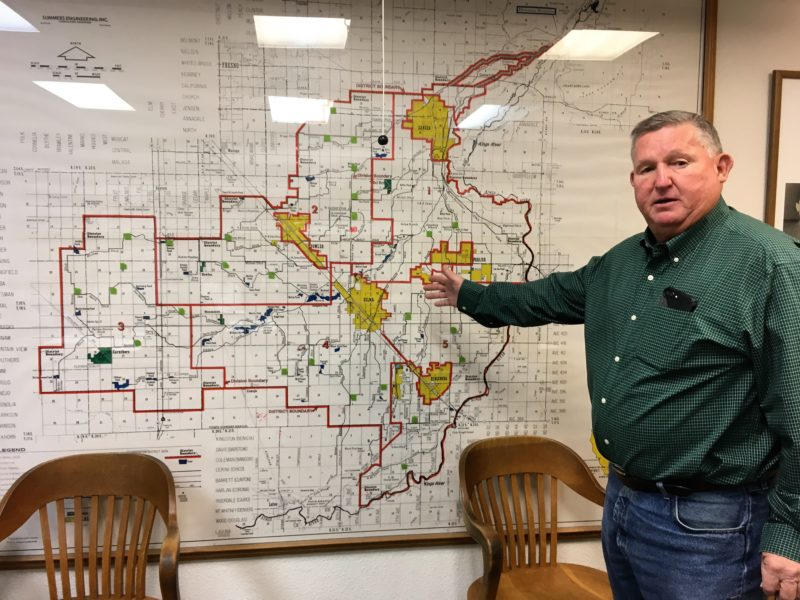 Photo of Phil Desatoff pointing to a map of water projects