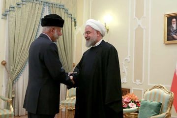 Photo of President Hassan Rouhani, right, shakes hands with Omani Minister of State for Foreign Affairs Yusuf bin Alawi