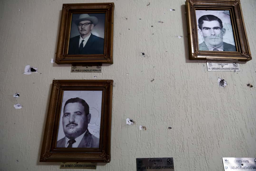 Photo of portraits of former mayors hang on a wall riddled with bullet holes, Mexico