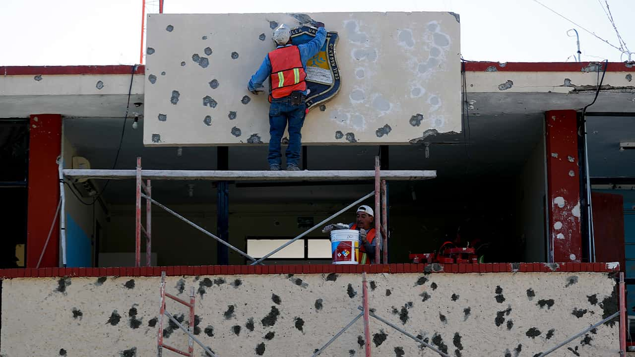 Photo of workers repairing the damage done to the facade of City Hall, Mexico