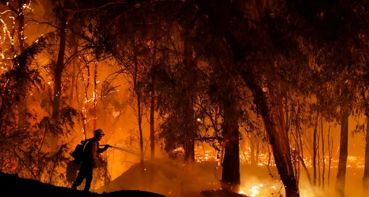 Photo of firefighter battling a wildfire in California