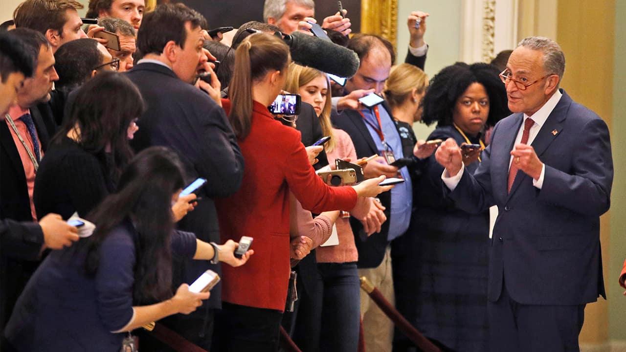 Photo of Senate Minority Leader Chuck Schumer, D-N.Y., right, talking to media