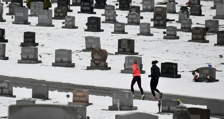 Photo of joggers running through a cemetery