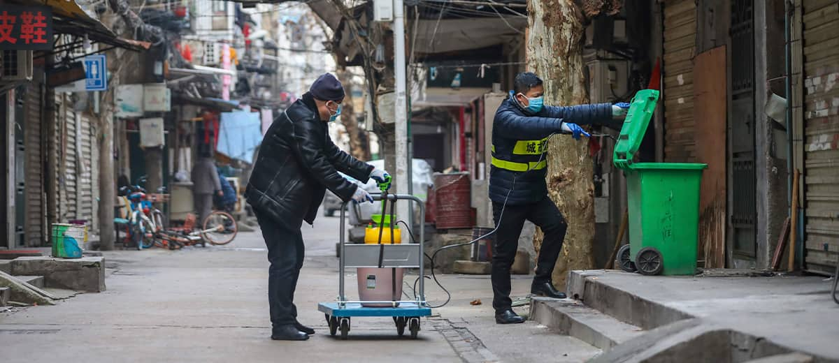 Photo of government workers spraying disinfectant on a garbage can in Wuhan