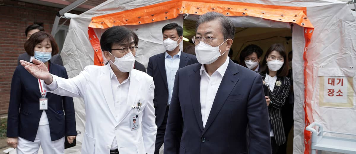 Photo of South Korean President Moon Jae-in, right, wearing a mask arriving to inspect the National Medical Center in Seoul, South Korea