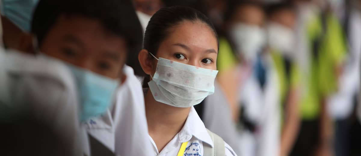 Photo of students lining up to sanitize their hands before a morning class in Cambodia