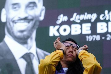 Photo of a woman wiping tears from her eyes at a Kobe Bryant memorial at the Staples Center in Los Angeles