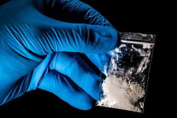 Photo of a gloved hand lifting up a package of powdered fentanyl