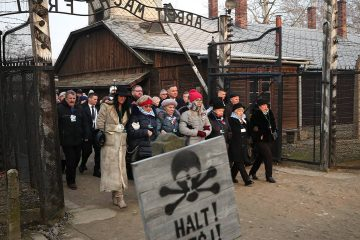 Poland's President Andrzej Duda walking along with survivors through the gates of the Auschwitz Nazi concentration camp to attend the 75th anniversary of its liberation
