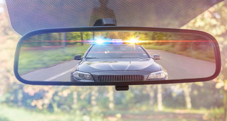 Photo of a cop car seen through a rear-view mirror