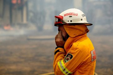 Photo of a firefighter covering his face