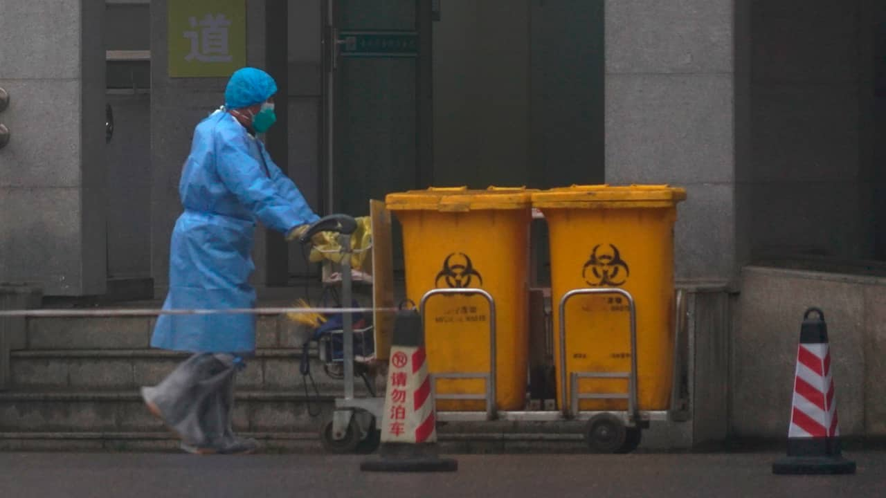 Photo of hospital staff moving bio-waste containers