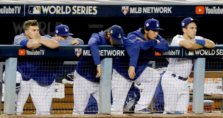 Photo of members of the Los Angeles Dodgers watching the Houston Astros celebrate their win in Game 7 of baseball's World Series in Los Angeles