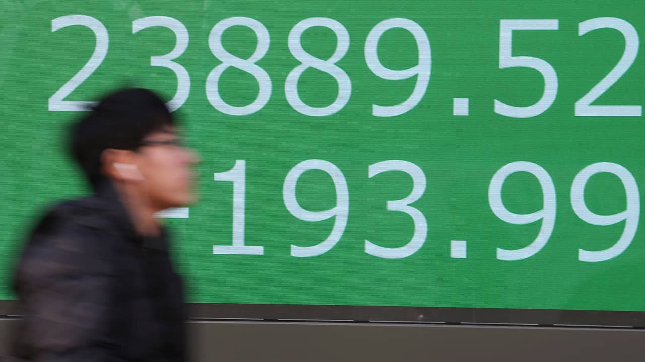 Photo of a man walking by an electronic stock board of a securities firm in Tokyo