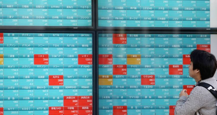 Photo of a man looking at an electronic stock board of a securities firm in Tokyo