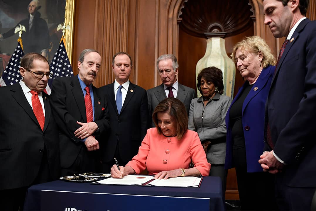 Photo of Nancy Pelosi signing the resolution to transmit the articles of impeachment