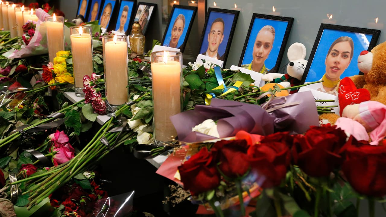 Photo of flowers and candles surrounding portraits of the flight crew members on the Ukrainian plan that crashed