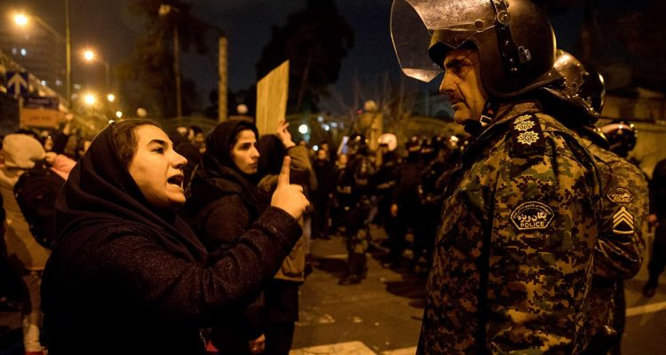 Photo of an Iranian protester talking to a policeman
