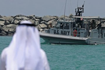 Photo of a Navy patrol boat carrying journalists see damaged oil tankers