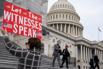 Photo of A woman holding a sign for members of the House