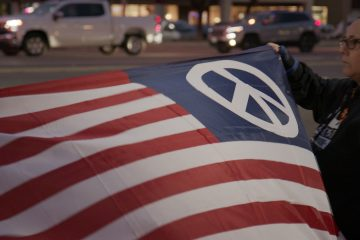 Photo of an American flag with a peace symbol