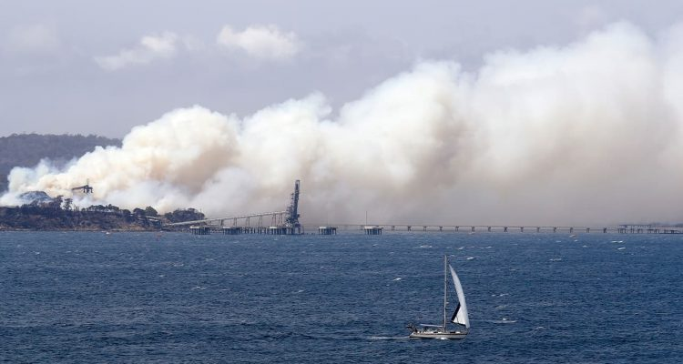 Photo of yacht sailing past a burning woodchip mill