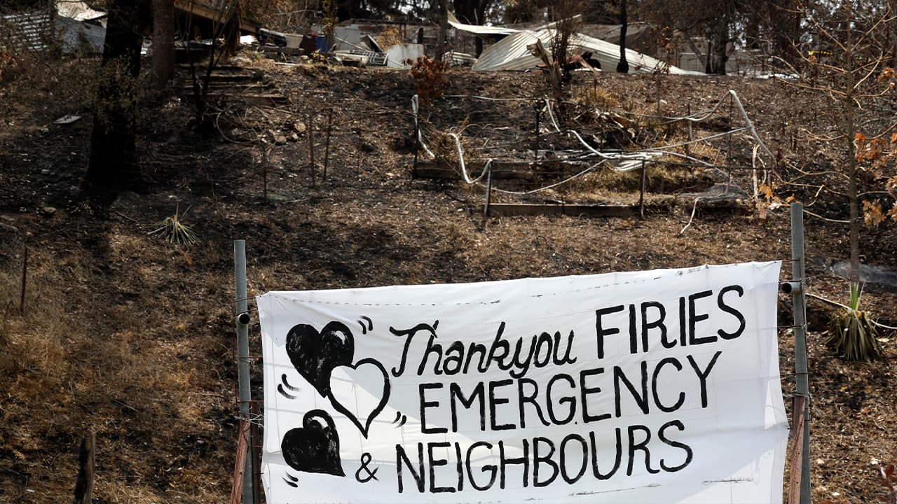 Photo of a sign displayed beside a burned house in Australia