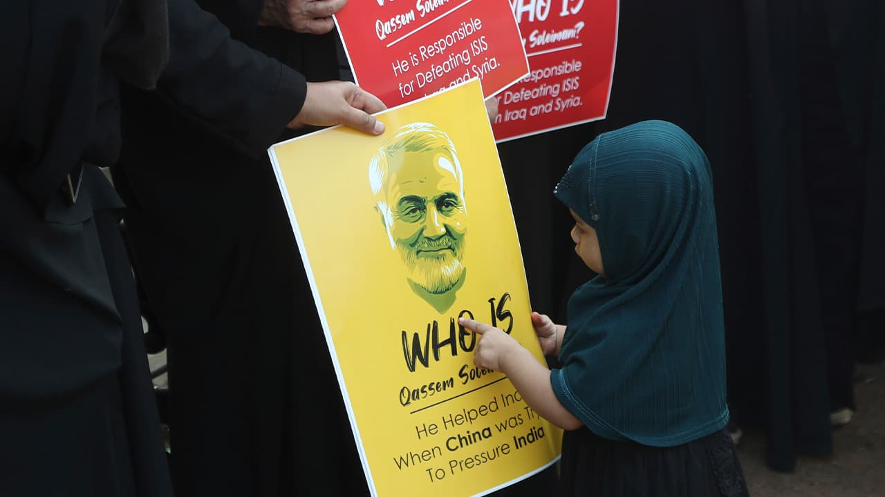 Photo of an Indian Shiite Muslim girl points at a portrait of Iranian Gen. Qassem Soleimani