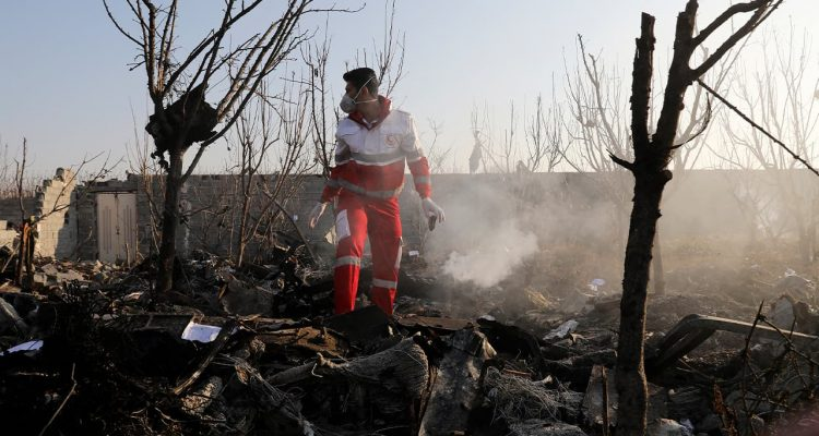 Photo of a rescue worker searching the scene where a Ukrainian plan crashed