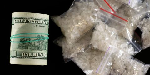 Photo of a roll of money and dime bags of meth