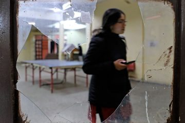 Photo of a student seen through broken glass