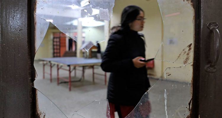 Photo of a student seen through broken glass