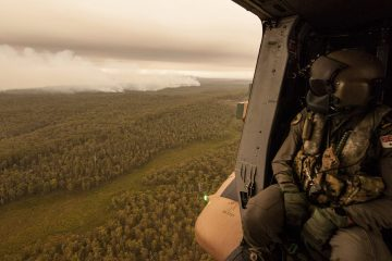 Photo of a Royal Australian Navy MRH-90 helicopter crew member looks out over fires burning near Cann River, Australia