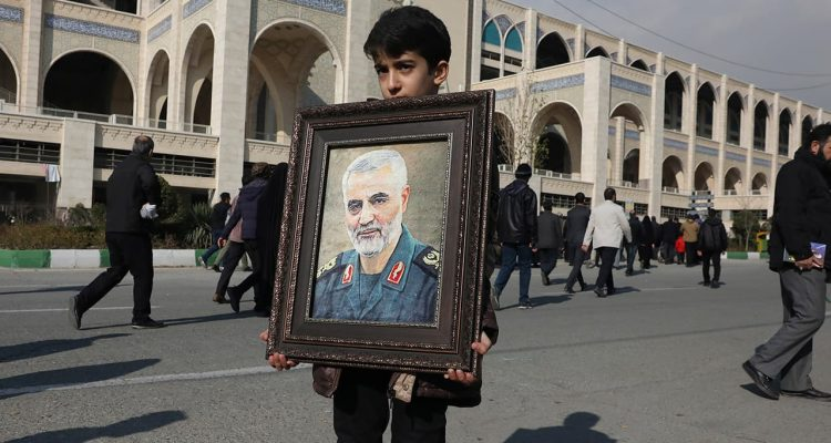 Photo of a boy holding a portrait of Iranian Revolutionary Guard Gen. Qassem Soleimani, who was killed in the U.S. airstrike in Iraq