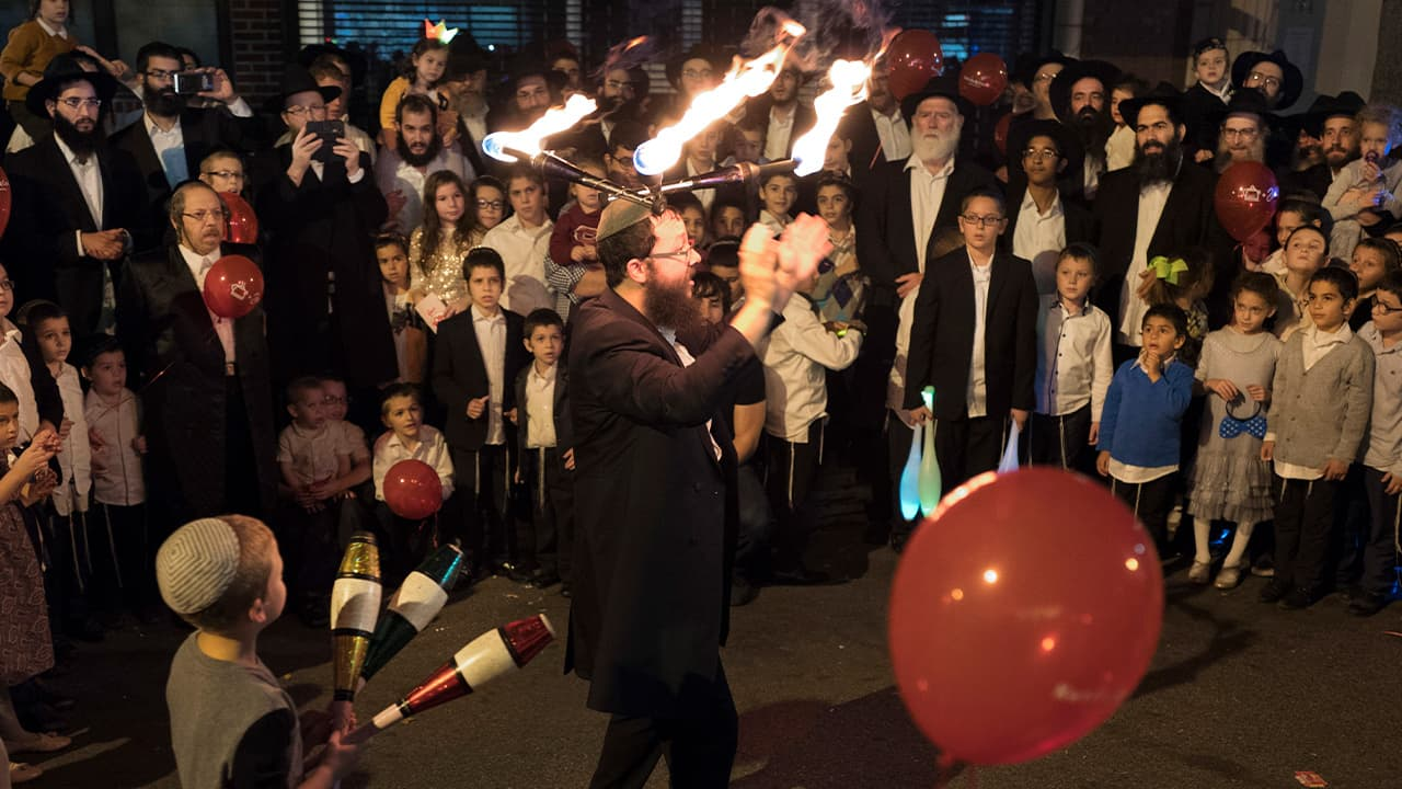 Photo of a performer wearing lighted sticks on his head while entertaining a crowd during the Jewish holiday of Sukkot