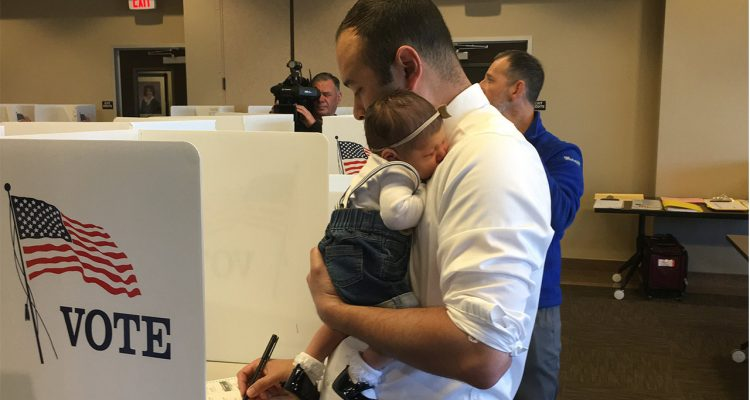 Photo of Andrew Janz voting with his daughter
