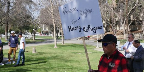 Photo of a man holding a sign at a Hmong rally