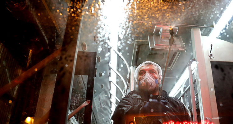 Photo of a worker disinfecting a public bus in Tehran, Iran