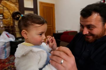 Photo of Abdullah Mohammed with his daughter, three-year-old Salwa inside a house he recently fled to, near the Syrian-Turkish border, in Sarmada, Syria