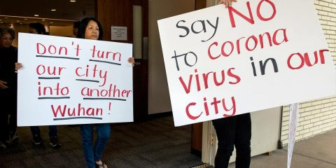 Photo of protesters holding signs in Costa Mesa, Calif.