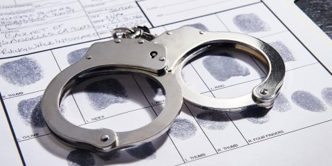 Photo of handcuffs on top of a fingerprint record