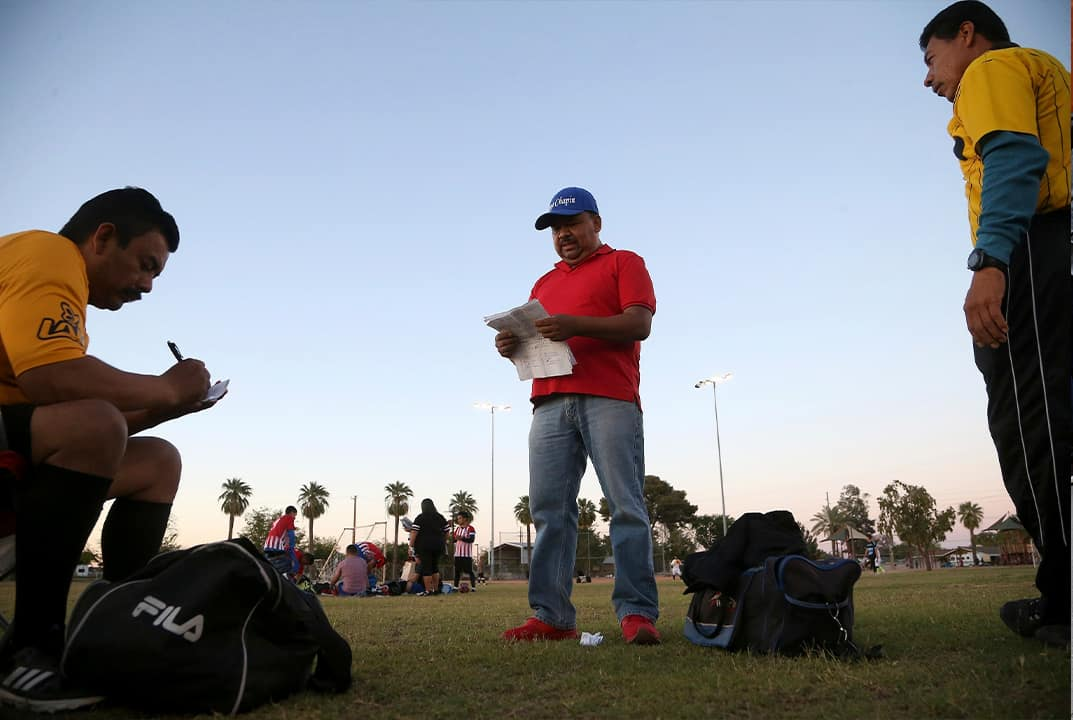 Photo of Antonio Velasquez, center, a pastor and director of the Maya Chapin soccer league