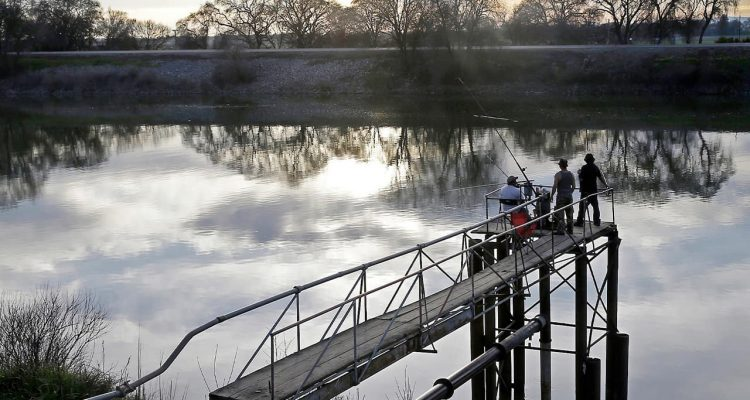 Photo of people trying to catch fish along the Sacramento River in the San Joaquin-Sacramento River Delta, near Courtland, Calif.