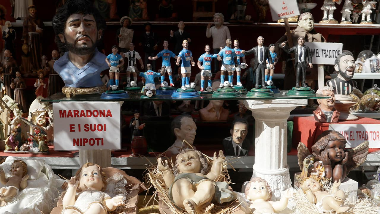 Photo of a placard reading Maradona and his nephew displayed in a shop with the statuettes of soccer legend and former Napoli player Diego Armando Maradona together with nativity scenes ones