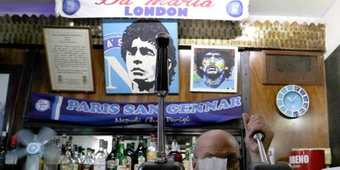 Photo of a bar tender preparing an espresso coffee inside the Bar Nilo where a makeshift shrine of soccer legend and former Napoli player Diego Armando Maradona is displayed