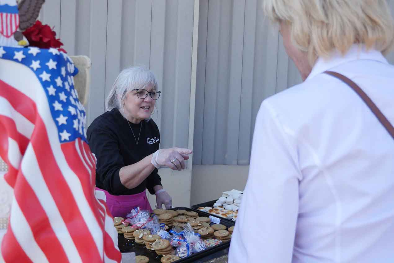 Photo of Tastries Bakery owner Cathy Miller handing out cookies in Bakersfield, Californiaent