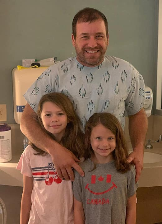 Photo of Ryan Newman with his daughters at the hospital
