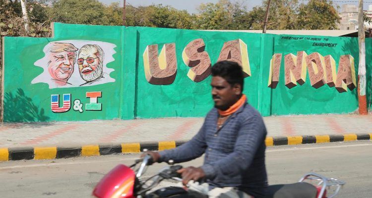 Photo of a man riding past a wall with portraits of U.S. President Donald Trump and Indian Prime Minister Narendra Modi