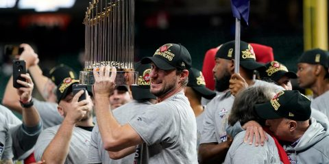 Photo of Washington Nationals starting pitcher Max Scherzer with the trophy after Game 7 of the baseball World Series against the Houston Astros in Houston
